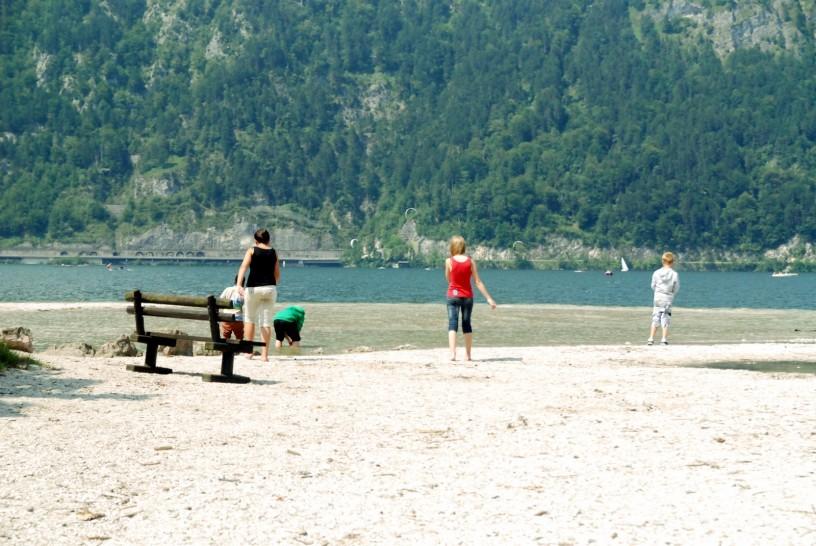 Ein See in den Bergen, davor ein paar Menschen, die mit den Füßen im Wasser plantschen.